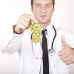 A doctor holding grapes giving a thumbs up sign