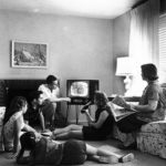 Blakc and white picture of 1958 family gathered around the television.